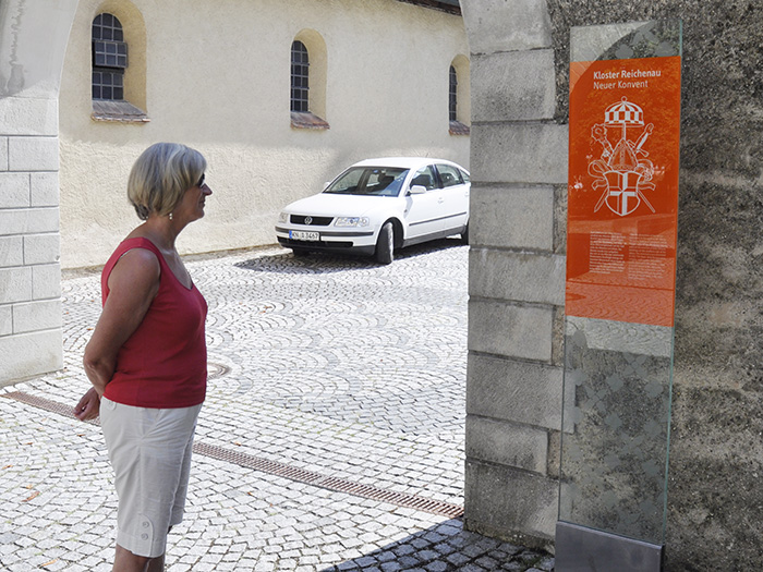woman reading glass destination sign with historic site description - brian switzer, envision+